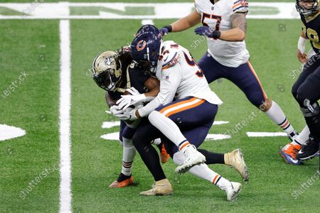 New Orleans Saints running back Alvin Kamara (41) is tackled by Chicago Bears outside linebacker Robert Quinn (94) during an NFL wild-card playoff football game, in New Orleans. The Saints defeated the Bears 21-9