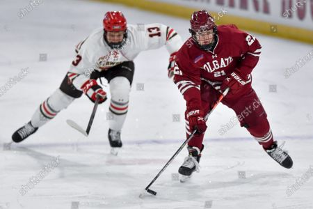 Colgate forward Alex Young (21) skates the puck away from St. Lawrence forward Aleksi Peltonen (13) during the first period of an NCAA hockey game on in Canton, N.Y