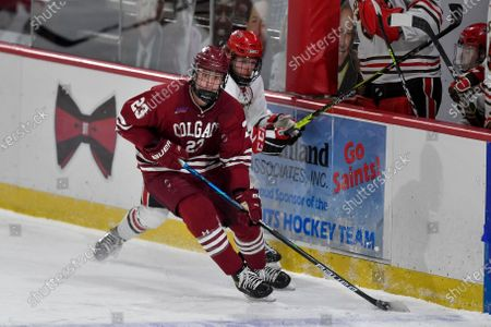 Colgate forward Jeff Stewart (23) skates with the puck in front of St. Lawrence forward Cameron Buhl (21) during the third period of an NCAA hockey game on in Canton, N.Y