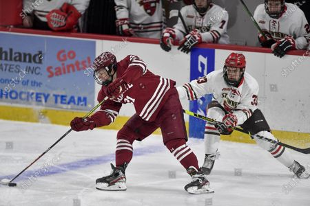 Colgate forward Alex Young (21) turns the puck away from St. Lawrence defenseman Tim Makowski (33) during the third period of an NCAA hockey game on in Canton, N.Y