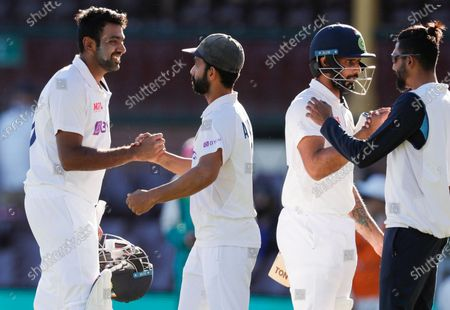 India's Ravichandran Ashwin, left, is congratulated by his captain Ajinkya Rahane as Hanuma Vihari is congratulated by teammate Mohammed Siraj, right, following play on the final day of the third cricket test between India and Australia at the Sydney Cricket Ground, Sydney, Australia, . The test ended in a draw and the series is at 1-1 all with one test to play