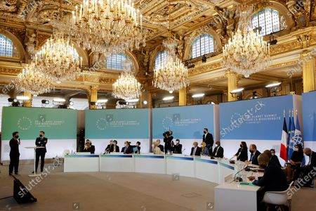 Stock Image of French President Emmanuel Macron (2 L), flanked by French singer Christophe Mae (L), speaks during the One Planet Summit, part of World Nature Day, at the Reception Room of the Elysee Palace, in Paris, France, 11 January 2021. The One Planet Summit, a largely virtual event hosted by France in partnership with the United Nations and the World Bank, will include French President, German Chancellor and European Union chief.