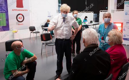 Stock Picture of Britain's Prime Minister Boris Johnson talks to Hazel and John Watson at Ashton Gate Stadium in Bristol, England. The center is one of the seven mass vaccination centers now opened to the general public as the government continues to ramp up the vaccination programme against Covid-19