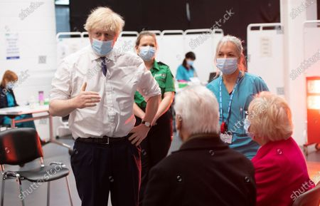 Stock Photo of Britain's Prime Minister Boris Johnson talks to Hazel and John Watson at Ashton Gate Stadium in Bristol, England. The center is one of the seven mass vaccination centers now opened to the general public as the government continues to ramp up the vaccination programme against Covid-19