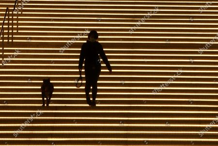 LOS ANGELES, CA - JANUARY 08, 2021 - Phedellee Reyes and her dog Marta are framed by illuminated steps descending from the Jerry Moss Plaza in Los Angeles on January 8, 2021. (Genaro Molina / Los Angeles Times)