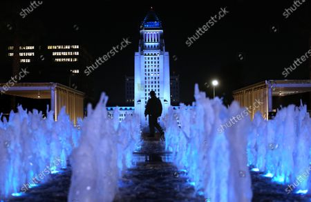 LOS ANGELES, CA - JANUARY 08, 2021 - A security officer is framed by Los Angeles' City Hall lit in Dodger blue tonight and through the weekend to honor the loss of former Los Angeles City Councilmember Tom LaBonge and Dodgers legend Tommy Lasorda as seen from Jerry Moss Plaza in Los Angeles on January 8, 2021. The blue cast on City Hall was requested by City Council President Nury Martinez and Mayor Eric Garcetti, according to Martinez' office. (Genaro Molina / Los Angeles Times)