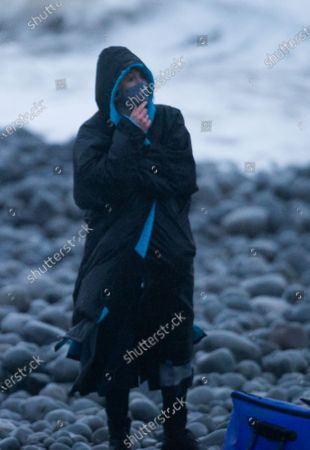 Jodie Whittaker wraps up against the weather between shoots on the shoreline near Barry, south Wales during Doctor Who filming