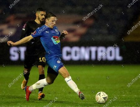 Stockport County's John Rooney, front, duels for the ball with West Ham's Manuel Lanzini during the English FA Cup third round soccer match between Stockport County and West Ham United at Edgeley Park in Stockport, England