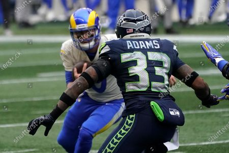 Seattle Seahawks strong safety Jamal Adams (33) takes aim on Los Angeles Rams quarterback John Wolford (9) as Wolford keeps the ball during the first half of an NFL wild-card playoff football game, in Seattle. Wolford left the game with an injury after the hit from Adams and was taken to a hospital in an ambulance as a precaution due to a neck injury on the play