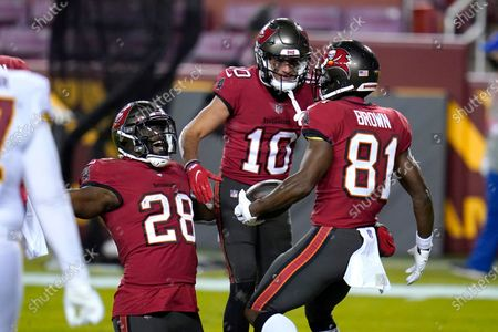Tampa Bay Buccaneers running back Leonard Fournette (28), wide receiver Scott Miller (10) and wide receiver Antonio Brown (81) celebrate Brown's touchdown catch against the Washington Football Team during the first half of an NFL wild-card playoff football game, in Landover, Md. Tampa Bay won 31-23