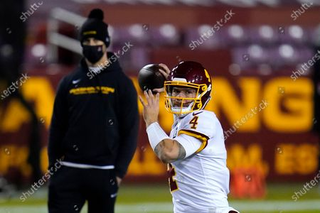 With Washington Football Team quarterback Alex Smith, back left, looking, quarterback Taylor Heinicke (4) works out prior to an NFL wild-card playoff football game against the Tampa Bay Buccaneers, in Landover, Md. Tampa Bay won 31-23