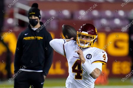 Stock Image of With Washington Football Team quarterback Alex Smith, back left, looking, quarterback Taylor Heinicke (4) works out prior to an NFL wild-card playoff football game against the Tampa Bay Buccaneers, in Landover, Md. Tampa Bay won 31-23