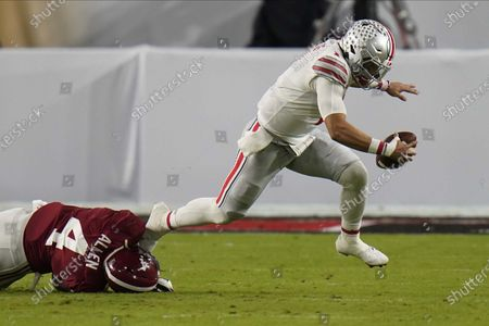 Stock Image of Ohio State quarterback Justin Fields is tackled by Alabama linebacker Christopher Allen during the first half of an NCAA College Football Playoff national championship game, in Miami Gardens, Fla