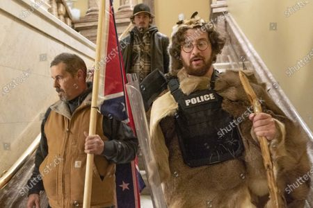 Supporters of President Donald Trump, including Aaron Mostofsky, right, who is identified in his arrest warrant, walk down the stairs outside the Senate Chamber in the U.S. Capitol, in Washington. Federal agents arrested Mostofsky, the son of a New York judge, on charges that he was among the protestors who stormed the U.S. Capitol, the FBI said on Tuesday, Jan. 12