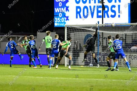 Sam Walker (1) of AFC Wimbledon is beaten by a headed shot at goal by Mark Little (2) of Bristol Rovers but is saved by the bar during the EFL Trophy match between Bristol Rovers and AFC Wimbledon at the Memorial Stadium, Bristol
