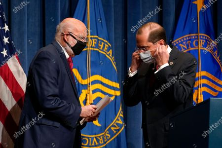 Dr. Robert Redfield, left, director of the Centers for Disease Control and Prevention, walks past Health and Human Services Secretary Alex Azar to speak during a news conference on Operation Warp Speed and COVID-19 vaccine distribution, in Washington