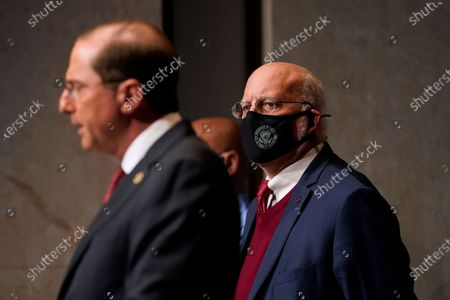 Dr. Robert Redfield, right, director of the Centers for Disease Control and Prevention, listens as Health and Human Services Secretary Alex Azar speaks during a news conference on Operation Warp Speed and COVID-19 vaccine distribution, in Washington