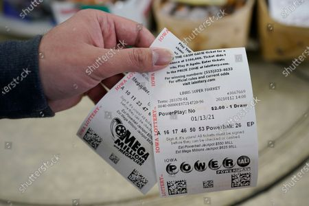 Hardik Kalra, of Des Moines, Iowa, holds his Mega Millions and Powerball lottery tickets, in Des Moines, Iowa. Lottery players have a chance to win the largest jackpots in nearly two years as Tuesday's Mega Millions has grown to an estimated $625 million and Wednesday's Powerball to an estimated $550 million