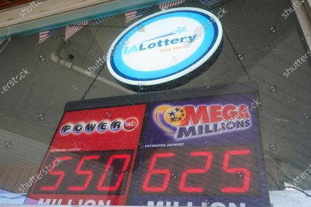 Lottery sign displaying jackpot amounts hangs in the window of a grocery store, in Des Moines, Iowa. Lottery players have a chance to win the largest jackpots in nearly two years as Tuesday's Mega Millions has grown to an estimated $625 million and Wednesday's Powerball to an estimated $550 million