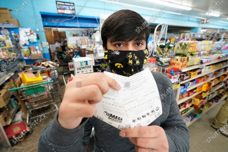 Hardik Kalra, of Des Moines, Iowa, poses for a photo with his Mega Millions and Powerball lottery tickets, in Des Moines, Iowa. Lottery players have a chance to win the largest jackpots in nearly two years as Tuesday's Mega Millions has grown to an estimated $625 million and Wednesday's Powerball to an estimated $550 million