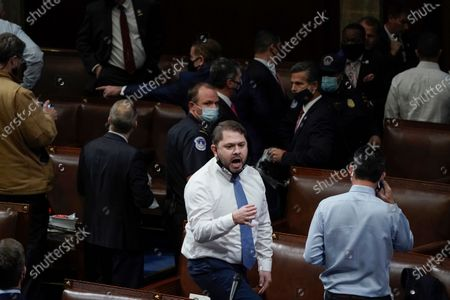 Stock Image of Rep. Ruben Gallego, D-Ariz., stands on a chair as lawmakers prepare to evacuate the floor as rioters try to break into the House Chamber at the U.S. Capitol, in Washington