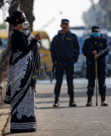 A demonstrator of the Bibekshil Sajha Party is dressed as Lady Justice during a protest against the dissolution of parliament near supreme court in Kathmandu, Nepal. 13 January 2021. The full bench of constitutional court started hearing the petitions against the dissolution of parliament at the Supreme Court. President Bidhya Devi Bhandari announced the dissolution of Parliament at the request of K.P. Sharma Oli's cabinet on 20 December 2020.