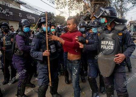 Stock Image of Nepalese police arrest activists of the Nepalese Student Union during the protest against dissolution of parliament in Kathmandua, Nepal, 13 January 2021. The full bench of constitutional court started hearing the petitions against the dissolution of parliament at the Supreme Court. President Bidhya Devi Bhandari announced the dissolution of Parliament at the request of K.P. Sharma Oli's cabinet on 20 December 2020.