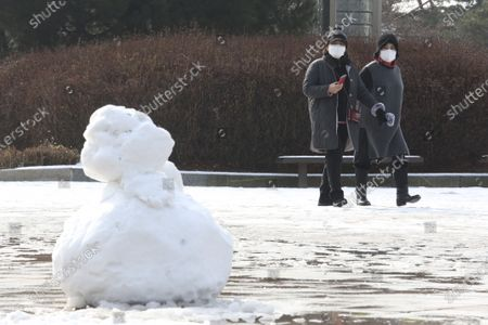 People wearing face masks to help curb the spread of the coronavirus pass by a melting snowman at a park in Goyang, South Korea