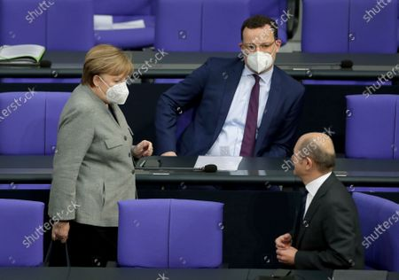 German Chancellor Angela Merkel, left, walks past German Health Minister Jens Spahn, center, and German Finance Minister Olaf Scholz, right, as she arrives for a meeting of the German federal parliament, Bundestag, at the Reichstag building in Berlin, Germany