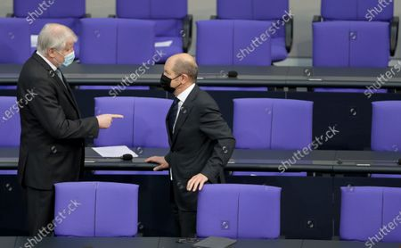 German Interior Minister Horst Seehofer, left, and German Finance Minister Olaf Scholz, right, talk as they arrive for a meeting of the German federal parliament, Bundestag, at the Reichstag building in Berlin, Germany, . One topic of the meeting are the current developments of the new coronavirus pandemic in Germany