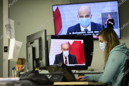 Stock Picture of A journalist wearing a face mask watches TV screens displaying Swiss Interior and Health Minister Alain Berset (top) and Swiss President Guy Parmelin (L) speaking during a press conference in Bern inside an office announcing new measures against the Coronavirus (COVID-19) in Lausanne, Switzerland, 13 January 2021.