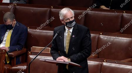 """Stock Photo of United States Representative Tom McClintock (Republican of California) makes remarks during the debate on H. Res. 24, the US House Impeachment resolution in the US Capitol in Washington, DC. Rep. McClintock's mask reads """"This mask is as useless as our governor."""" This will be the second occasion where the US House has brought charges against US President Donald J. Trump."""