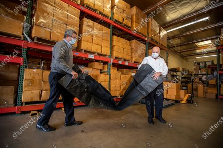 David Cameron, left, Executive Vice President, and Abdul Salam, president of Salam International, unpack a body bag in the warehouse. Salam International is a producer of body bags, morgue & mortuary supply equipment, precision instruments and pathology Tuesday, Jan. 5, 2021 in Laguna Hills, CA. (Allen J. Schaben / Los Angeles Times)