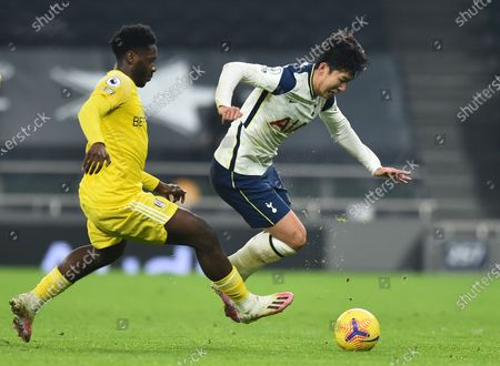 Fulham's Ola Aina, left, duels for the ball with Tottenham's Son Heung-min during the English Premier League soccer match between Tottenham Hotspur and Fulham at the Tottenham Hotspur Stadium in London