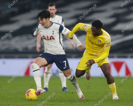Tottenham's Son Heung-min, left, duels for the ball with Fulham's Ola Aina during the English Premier League soccer match between Tottenham Hotspur and Fulham at the Tottenham Hotspur Stadium in London