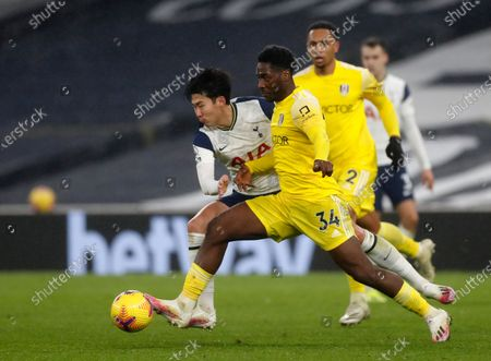 Fulham's Ola Aina, front, duels for the ball with Tottenham's Son Heung-min during the English Premier League soccer match between Tottenham Hotspur and Fulham at the Tottenham Hotspur Stadium in London