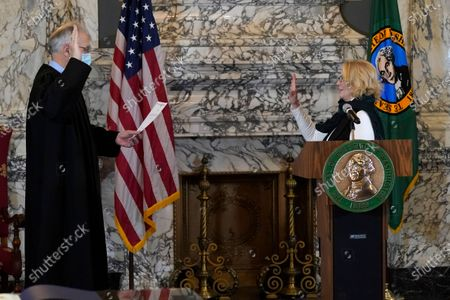 State Auditor Pat McCarthy, right takes her oath of office as administered by Washington Supreme Court Associate Chief Justice Charles Johnson, left, during a ceremony at the Capitol in Olympia, Wash