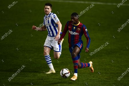Barcelona's Ousmane Dembele, right, vies for the ball with Real Sociedad's Igor Zubeldia during Spanish Super Cup semi final soccer match between Barcelona and Real Sociedad at Nuevo Arcangel stadium in Cordoba, Spain