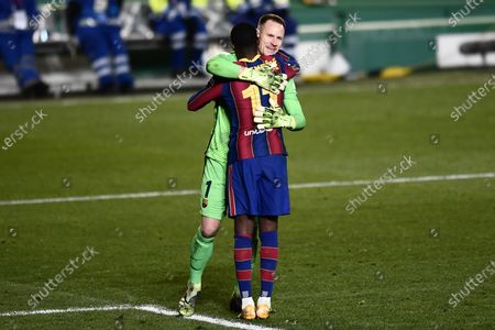Barcelona's goalkeeper Marc-Andre ter Stegen greets teammate Ousmane Dembele, front, during Spanish Super Cup semi final soccer match between Barcelona and Real Sociedad at Nuevo Arcangel stadium in Cordoba, Spain, . Barcelona will play the final after defeating Real Sociedad 3-2 in a penalty shootout after the game ended 1-1