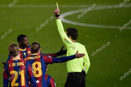 The referee shows yellow card to Ousmane Dembele of FC Barcelona during the Spain Supercup Semifinal 1 match between Real Sociedad and FC Barcelona played at El Arcangel Stadium on January 13, 2021 in Cordoba, Spain.