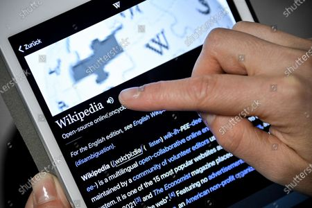 Stock Image of A close-up image shows a woman using the Wikipedia online encyclopedia on an iPad, in Cologne, Germany, 13 January 2021. The online encyclopedia Wikipedia was launched on 15 January 2001 by co-founder Jimmy Wales and is now one of the most visited website on the Internet. There are articles in around 300 languages, its service is still non-commercial, and the non-profit organization is financed solely by donations. More than three million volunteers write, edit and check the articles. Wikipedia has become a kind of basic knowledge of the world.