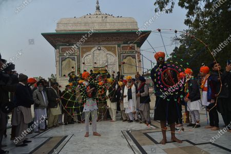 Stock Picture of Member of Pakistan Sikh Gurdwara Prabandhak Committee along with Member Provincial Assembly, Sardar Ramesh Singh Arora, Sardar Bishan Singh,Sardar Ameer Singh, Syed Ali Raza Qadri busy in religious rituals during showered flowers on the grave of Hazrat Mian Mir Bala Pir Sarkar the ceremony as Mian Mir Bala Pir Sarkar were Foundations Stone of the Golden Temple (Sri Harmandar Singh Sahib) for Sikh Community at India on 13 January 1588. in Lahore.