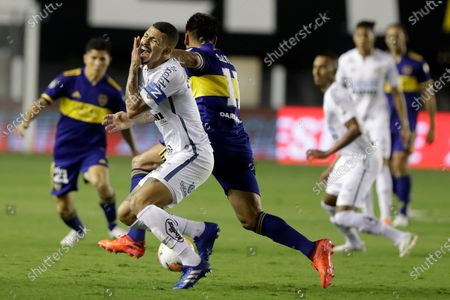 Alison of Brazil's Santos, left, and Eduardo Salvio of Argentina's Boca Juniors battle for the ball during a Copa Libertadores semifinal second leg soccer match in Santos, Brazil