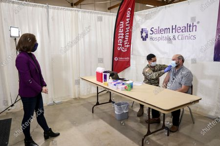 Oregon Gov. Kate Brown watches as a COVID-19 vaccine is administered by National Guard member Juan Carlos Rojas to Jason Mayberry at the Marion County and Salem Health vaccination clinic, at the Oregon State Fairgrounds in Salem, Ore