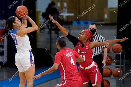 DePaul guard Sonya Morris shoots against St. John's forward Raven Farley, center, and guard Qadashah Hoppie during the first half of an NCAA college basketball game in Chicago
