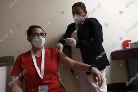 Pediatric nurse receives a dose of the Pfizer vaccine against COVID-19, on the first day of vaccinations in Ciudad Juarez, Mexico