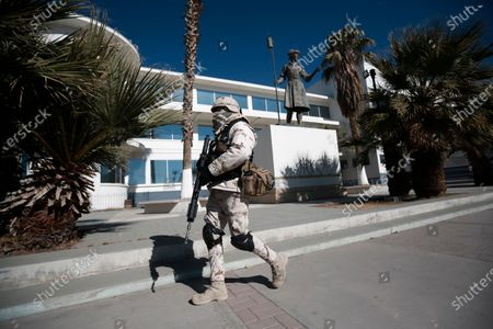 Soldier patrols outside General Hospital, one of the locations where medical workers were being given the Pfizer COVID-19, on the first day of coronavirus vaccinations in Ciudad Juarez, Mexico