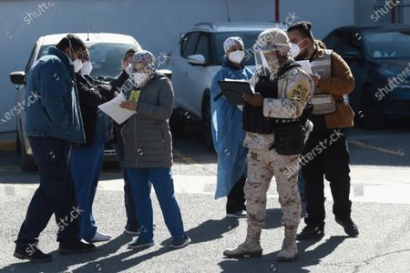 Medical workers are registered to receive the Pfizer COVID-19 vaccine, outside a vaccination center at General Hospital on the first day of coronavirus vaccinations in Ciudad Juarez, Mexico