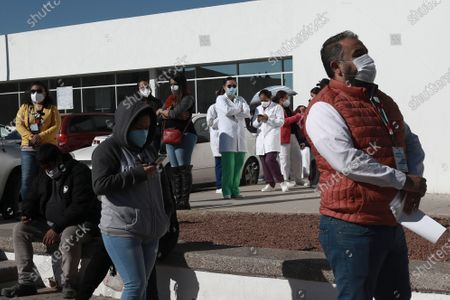 Health care workers wait in line outside General Hospital to receive the Pfizer COVID-19, on the first day of coronavirus vaccinations in Ciudad Juarez, Mexico