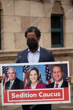 Robert Dempster, vice chairman of the Miami Dade Democratic Party, holds up a sign showing Florida Republican members of Congress Carlos Gimenez, Maria Elvira Salazar, and Mario Diaz Balart, during a news conference, in front of the Freedom Tower in downtown Miami. Miami-Dade County Democratic leaders condemned the three Florida Republican members who voted against the impeachment of President Donald Trump
